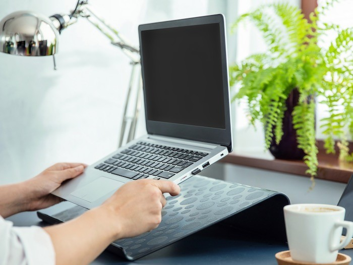 A desk with a laptop on a stand.