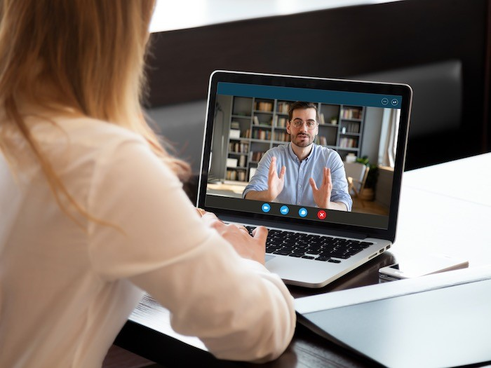 Two people on a video call, with view of one person's background with books.