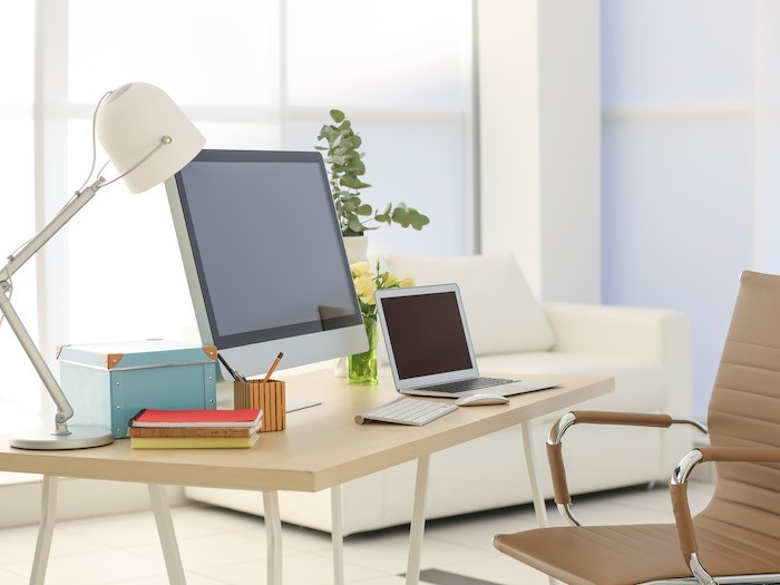 A desk facing natural light with a computer and desk lamp.